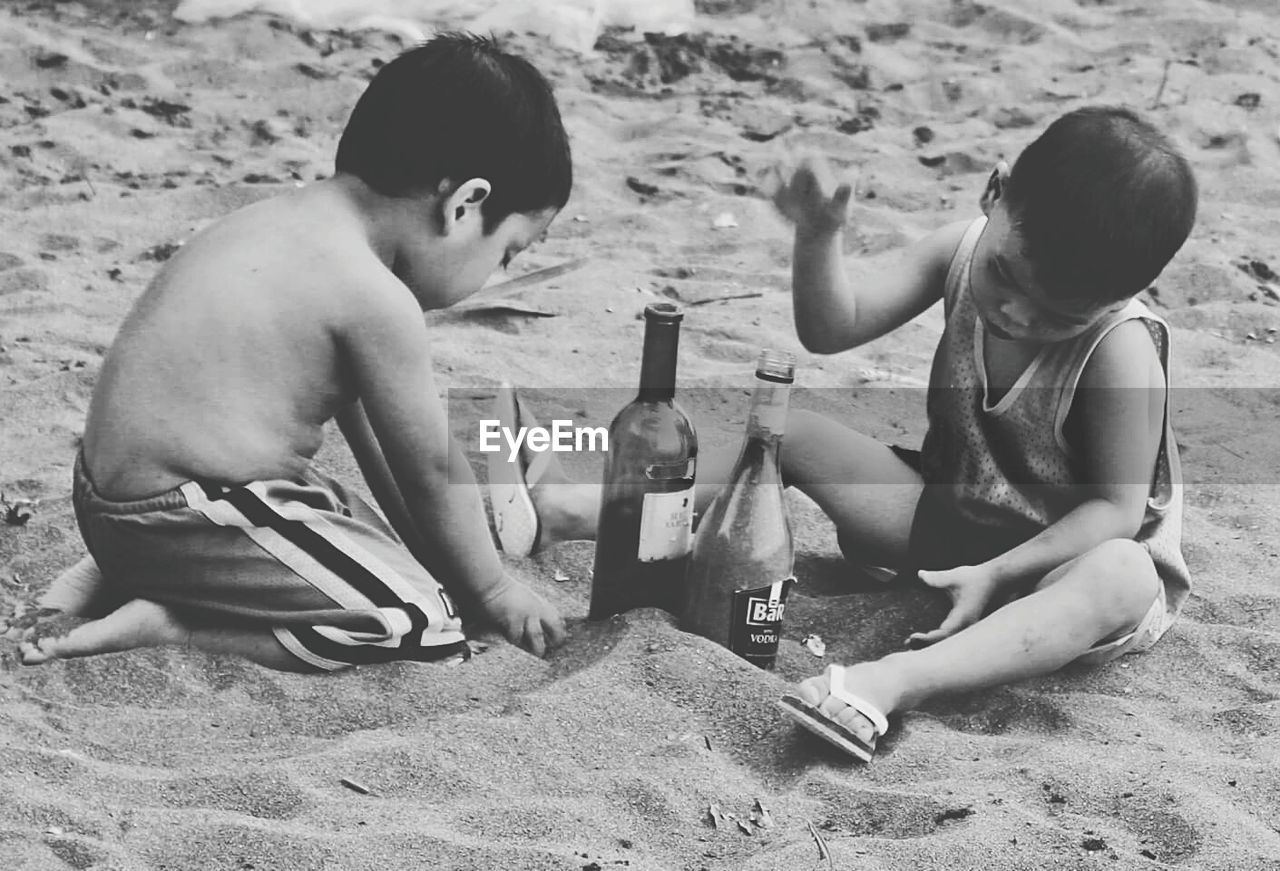 sand, childhood, beach, boys, sitting, elementary age, two people, togetherness, real people, outdoors, crouching, sand pail and shovel, leisure activity, day, vacations, bonding, fun, shirtless, playing, happiness, full length, girls, child, nature, friendship, animal themes, people