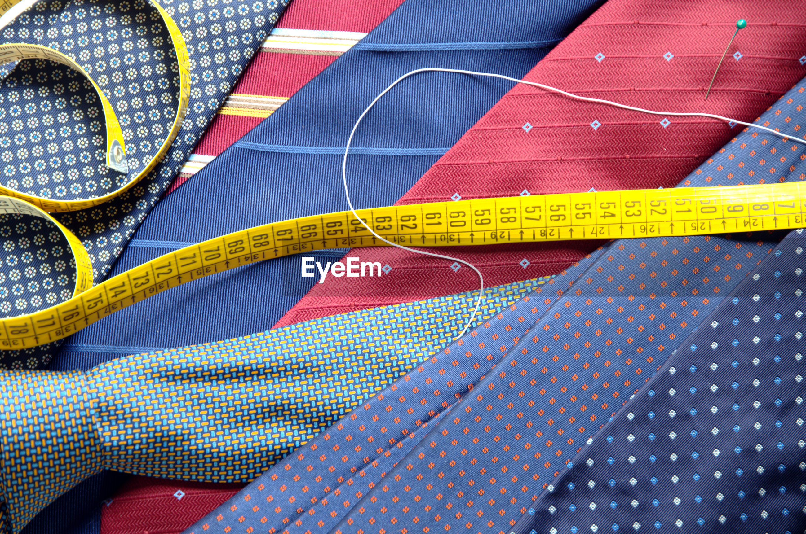 Close-up of colorful neckties with tape measure