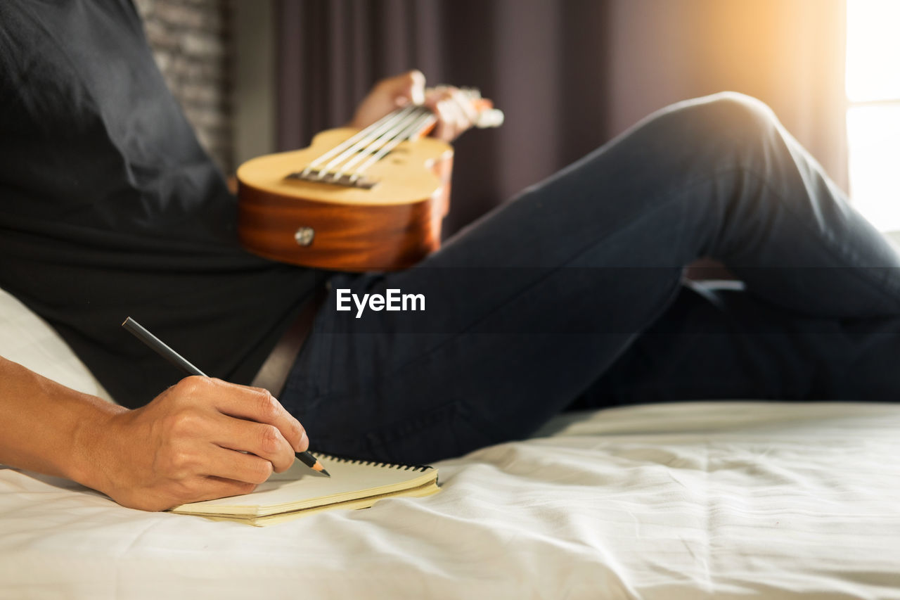 Midsection Of Man Writing On Spiral Notebook While Playing Guitar At Home