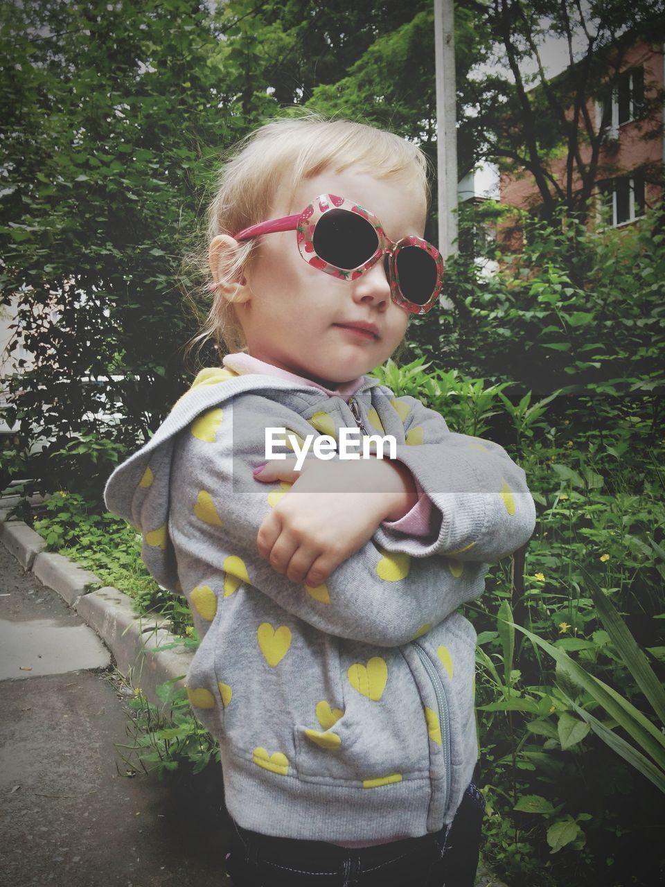 Portrait Of Cute Little Girl Standing By Plants In Yard
