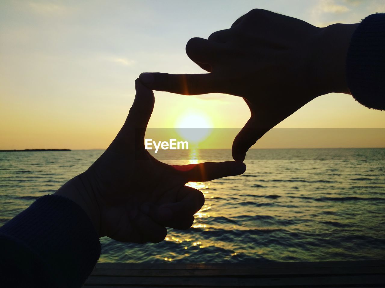 human hand, hand, sunset, sky, water, sea, sun, human body part, holding, nature, real people, one person, lifestyles, horizon over water, sunlight, tranquility, finger, beach, body part, outdoors, positive emotion