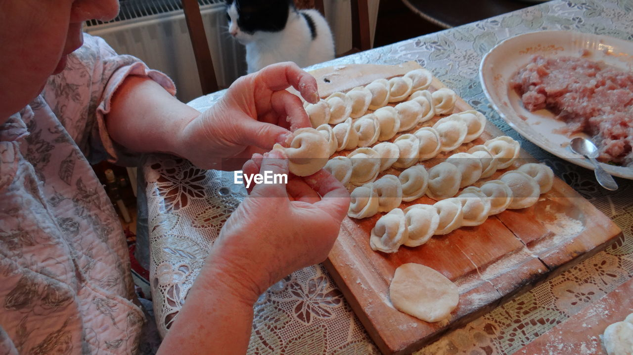 Midsection Of Woman Making Dumplings In Kitchen At Home
