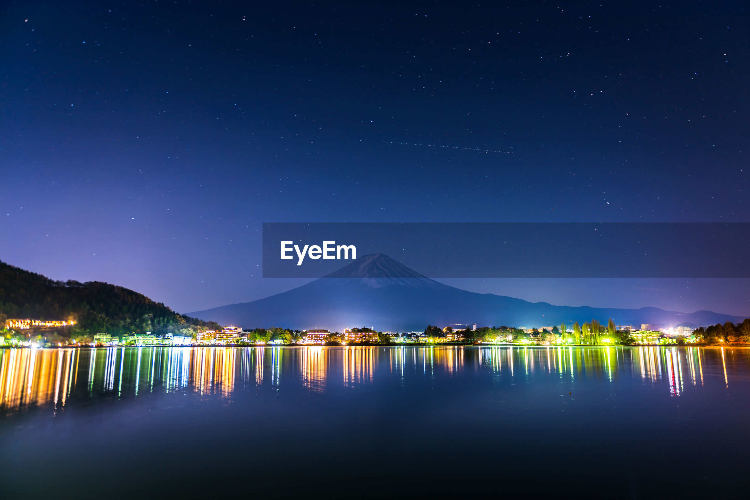 SCENIC VIEW OF LAKE BY ILLUMINATED MOUNTAINS AGAINST SKY AT NIGHT