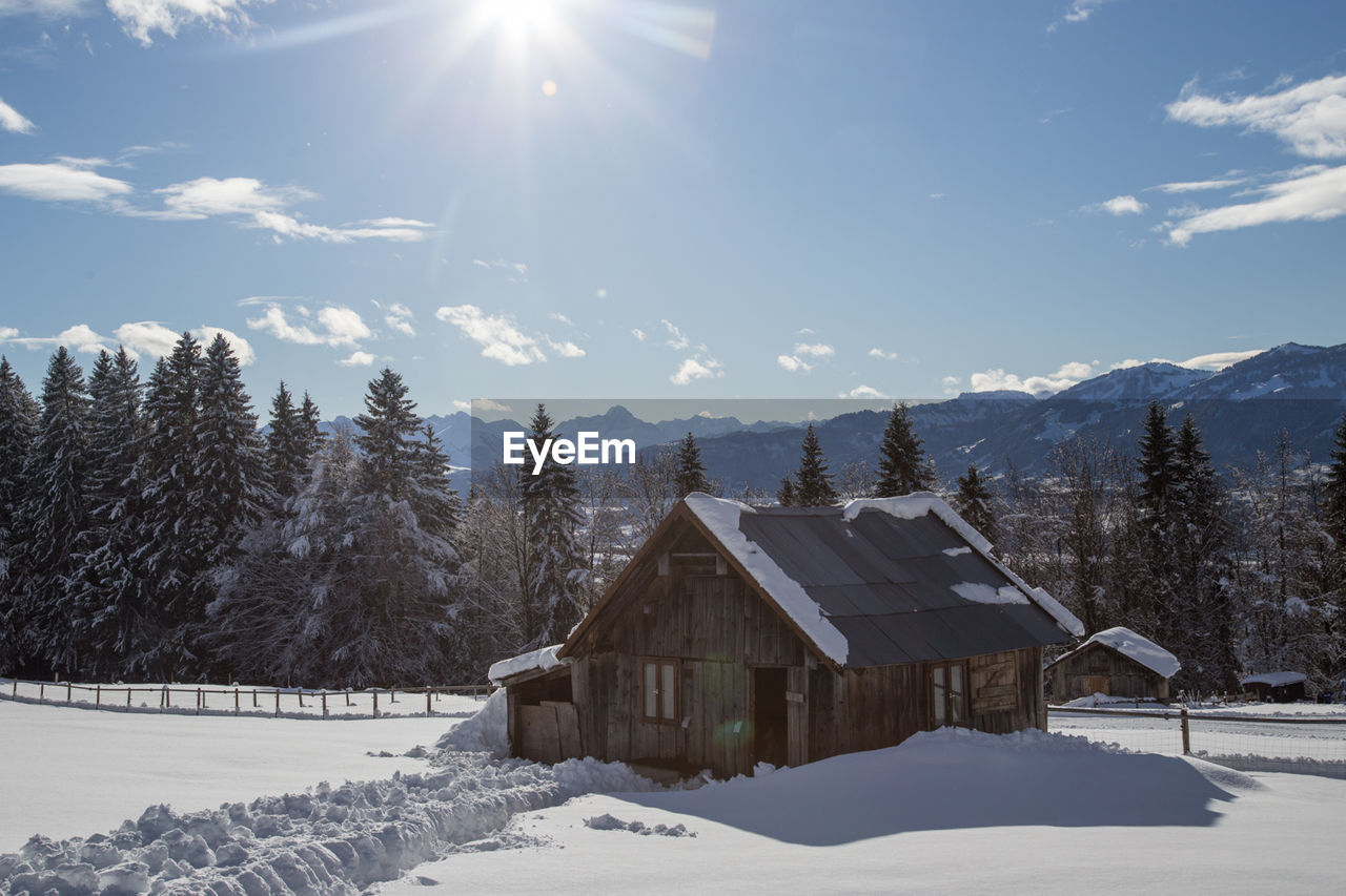snow, winter, cold temperature, sunlight, built structure, architecture, sunbeam, nature, house, tranquility, cold, sky, scenics, no people, weather, beauty in nature, building exterior, tree, sun, day, tranquil scene, outdoors, landscape, mountain
