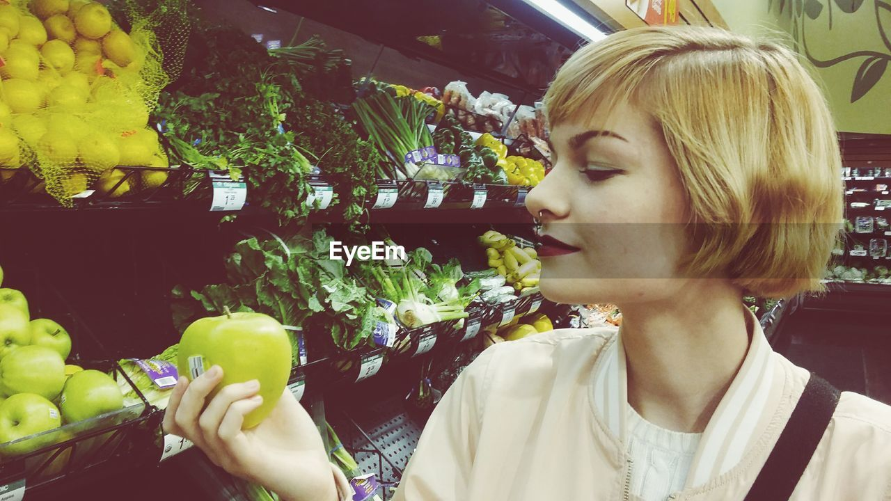 Close-Up Of Blond Woman Looking At Granny Smith Apple At Supermarket