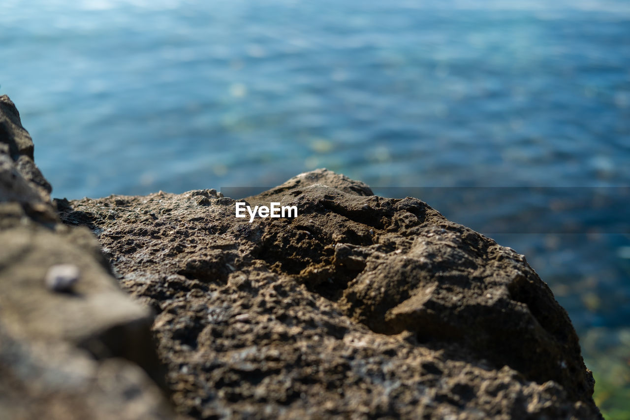 rock, solid, selective focus, rock - object, day, textured, nature, no people, sea, close-up, rough, water, outdoors, tranquility, land, focus on foreground, beauty in nature, beach, rock formation, lichen