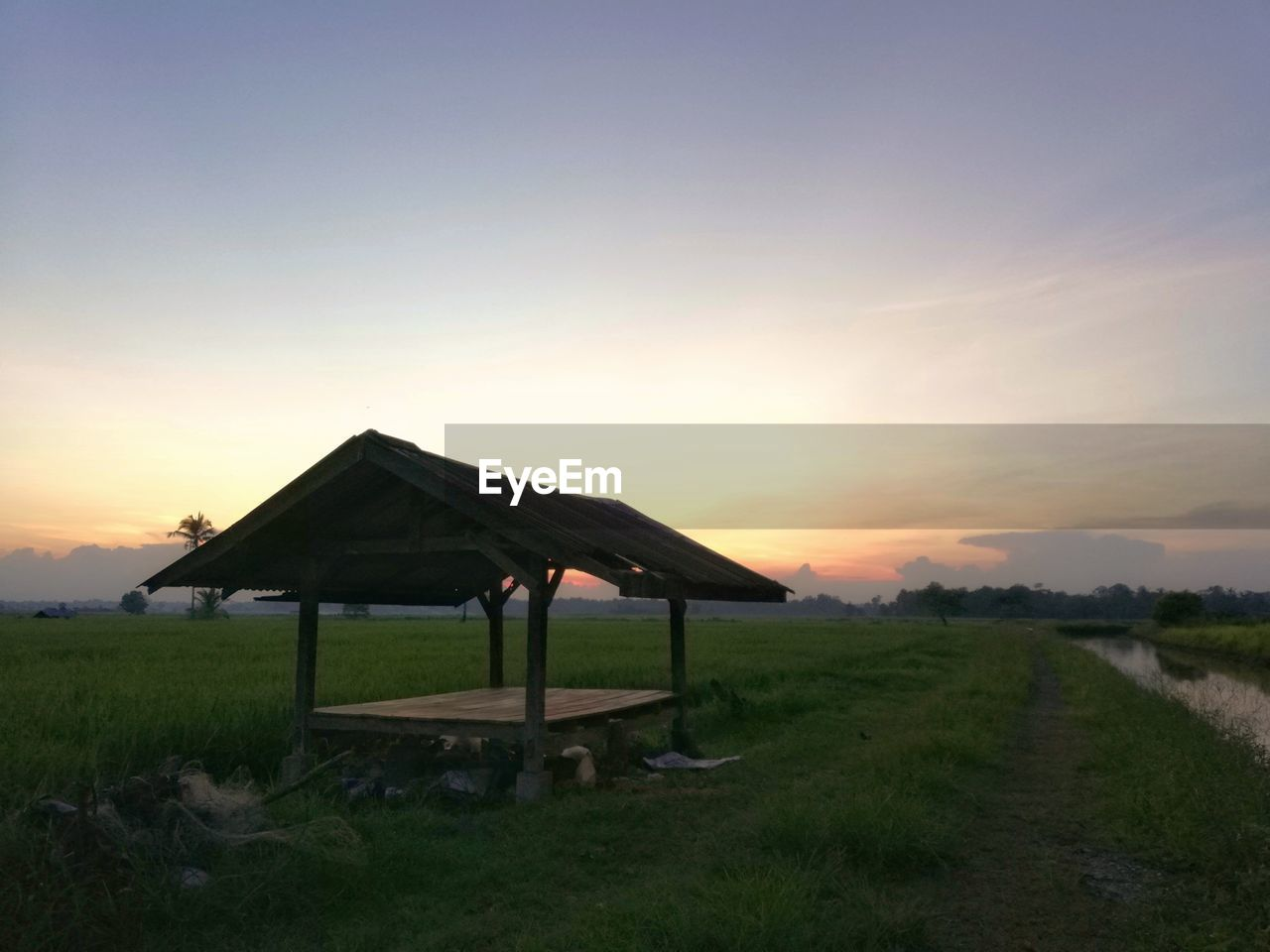 sky, sunset, grass, architecture, land, nature, field, landscape, built structure, environment, plant, tranquility, tranquil scene, beauty in nature, no people, scenics - nature, orange color, copy space, building exterior, agriculture, outdoors, sun
