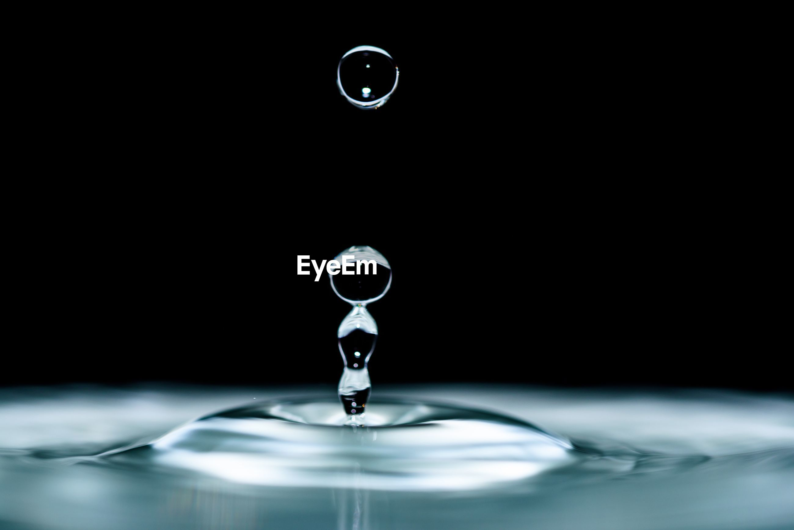 Close-up of drop falling in water against black background
