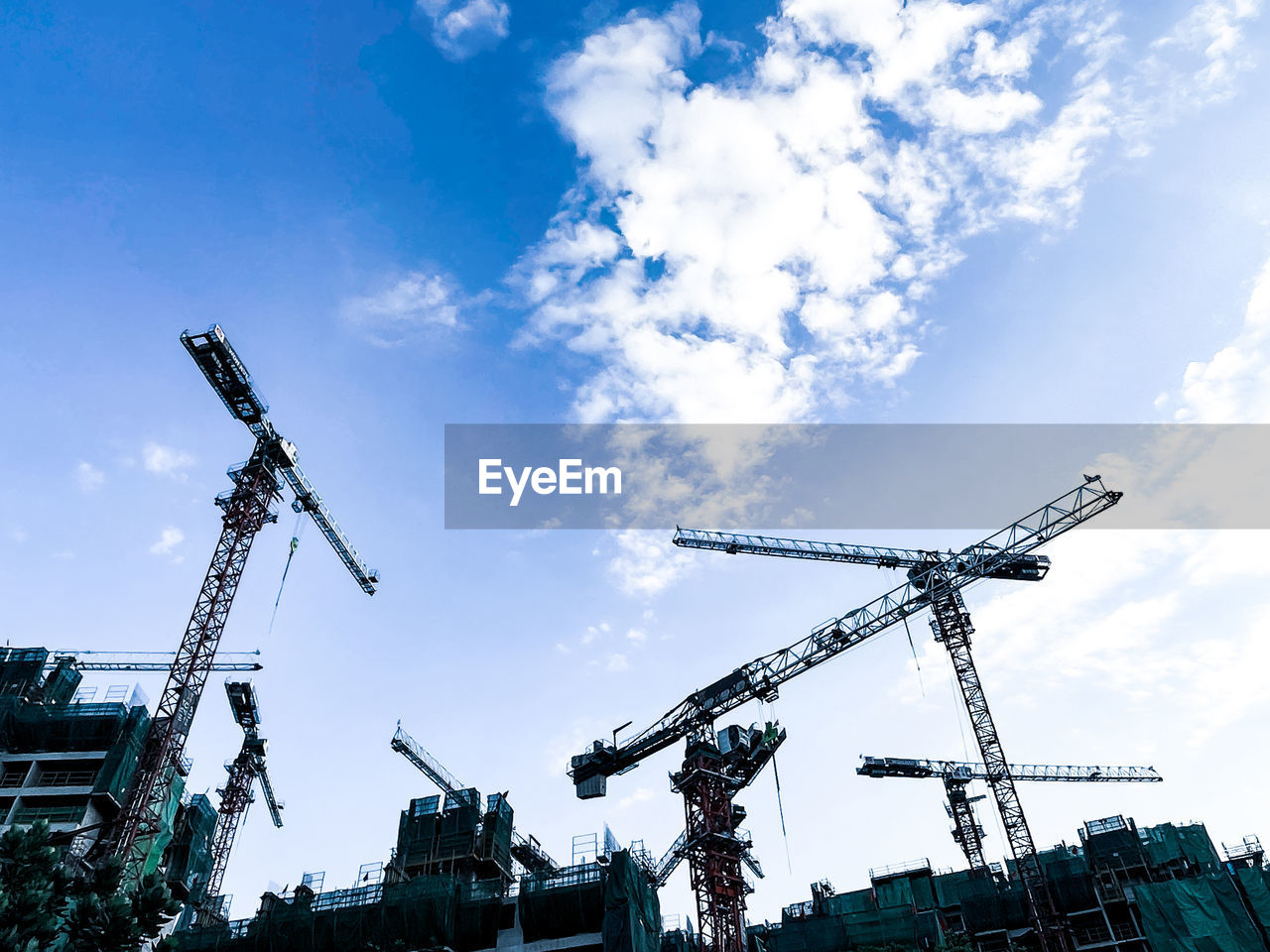 LOW ANGLE VIEW OF CRANES AGAINST CONSTRUCTION SITE
