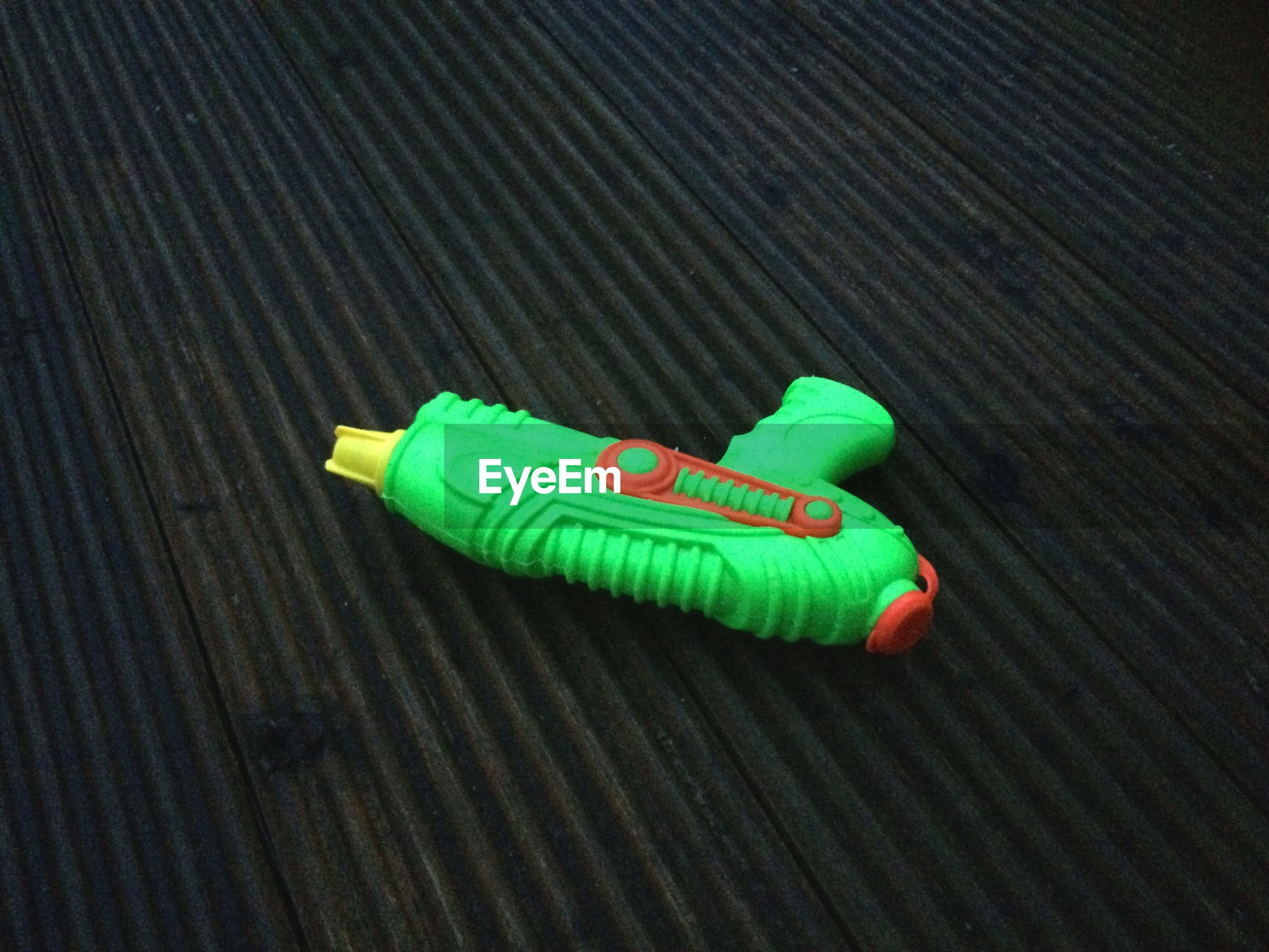 High angle view of green squirt gun on metal grate