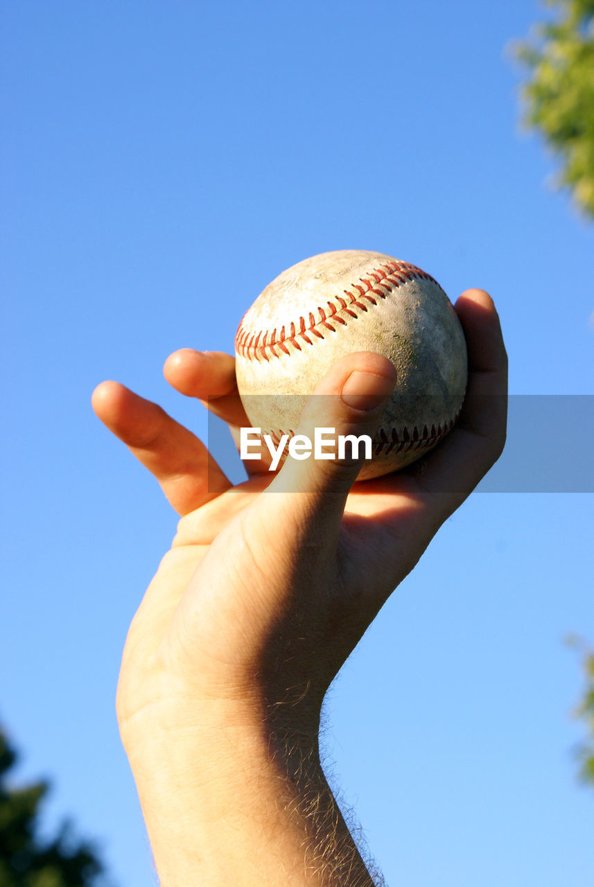 Low angle view of hand holding baseball against sky