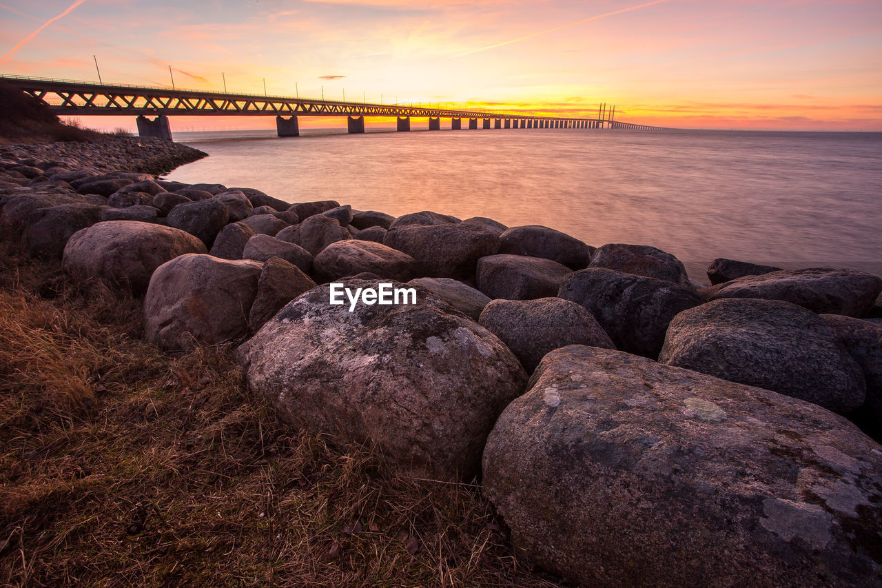 sunset, sky, water, sea, rock, connection, rock - object, solid, bridge, beauty in nature, nature, built structure, scenics - nature, architecture, cloud - sky, orange color, tranquility, bridge - man made structure, tranquil scene, no people, outdoors