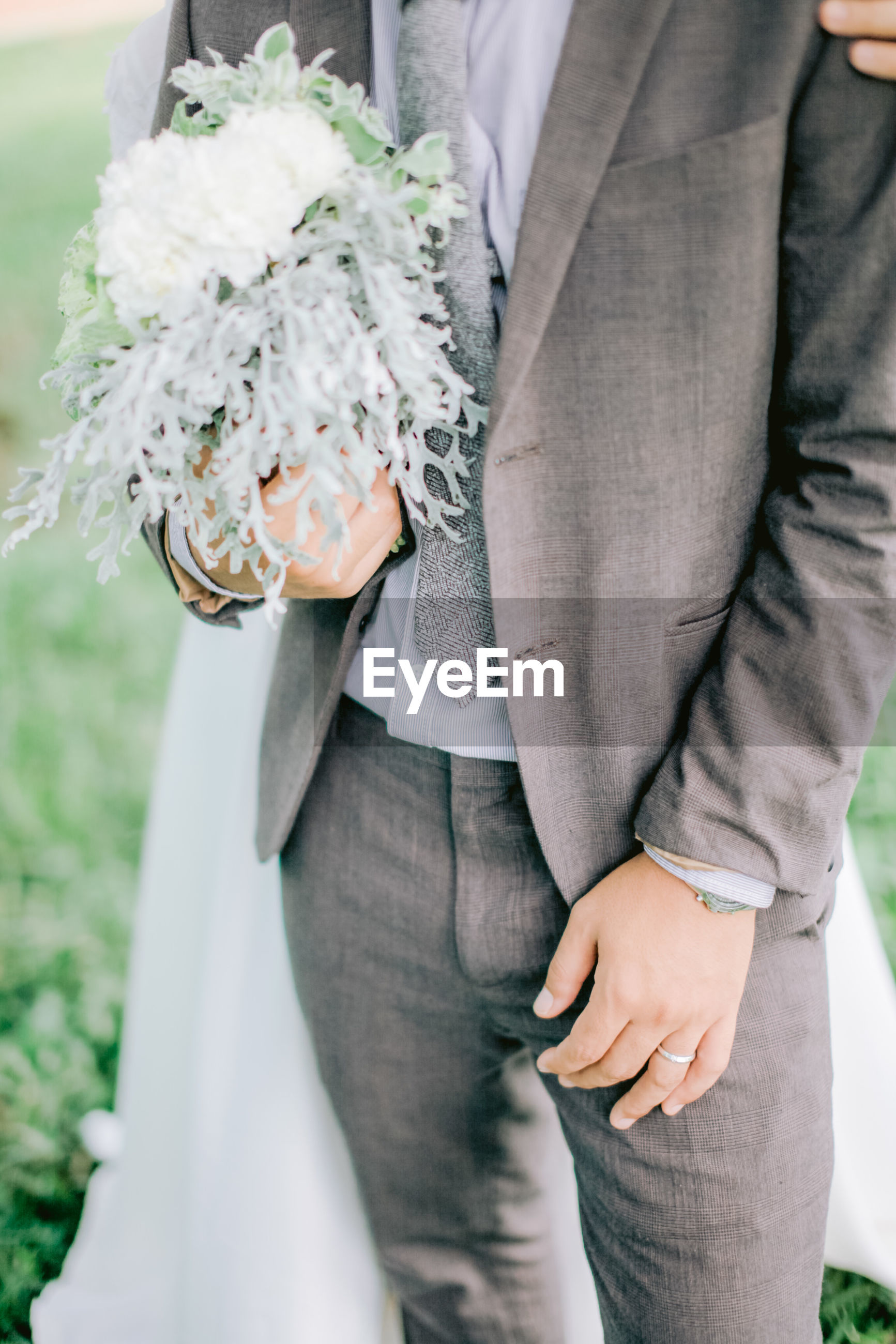 Midsection of couple holding bouquet