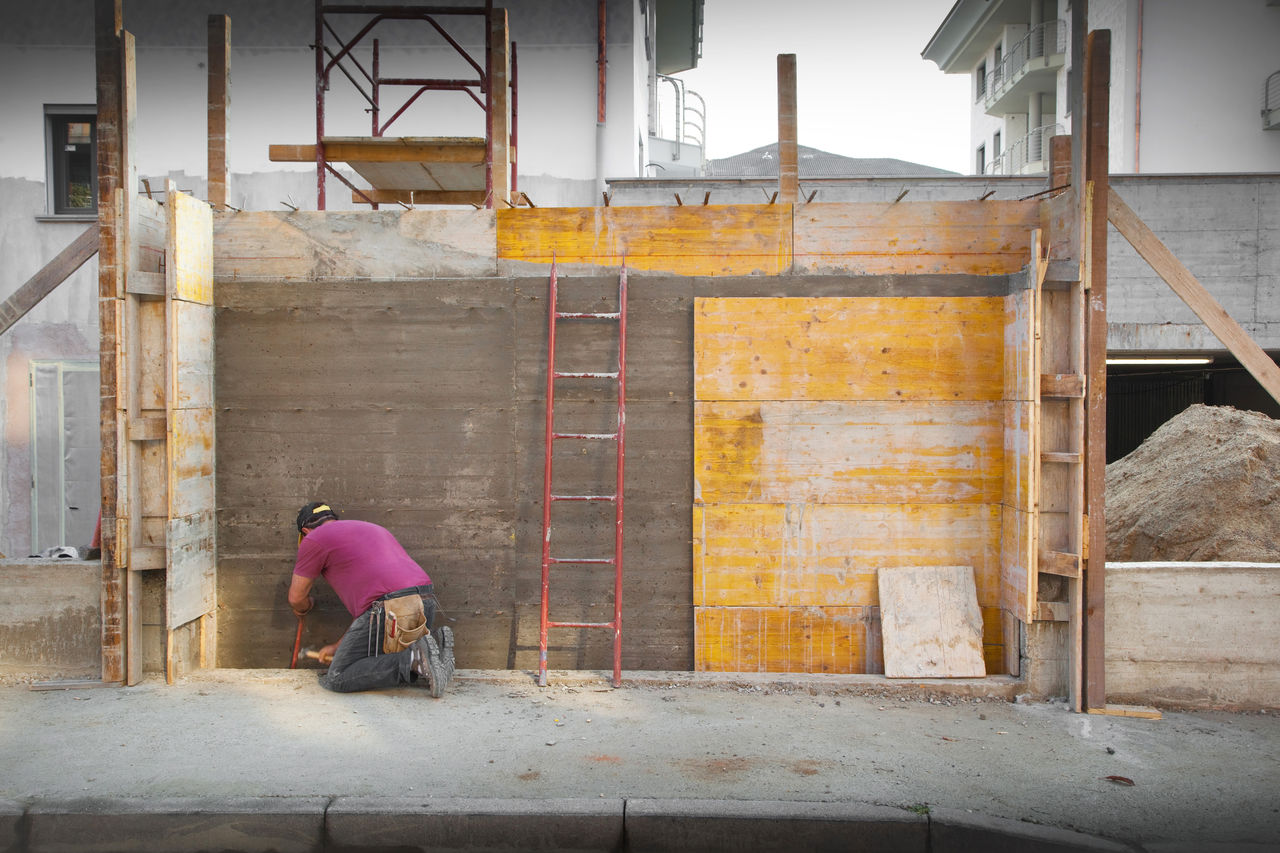 architecture, real people, building exterior, built structure, one person, building, day, full length, outdoors, rear view, protection, lifestyles, working, men, entrance, women, casual clothing, residential district, construction industry, waiting