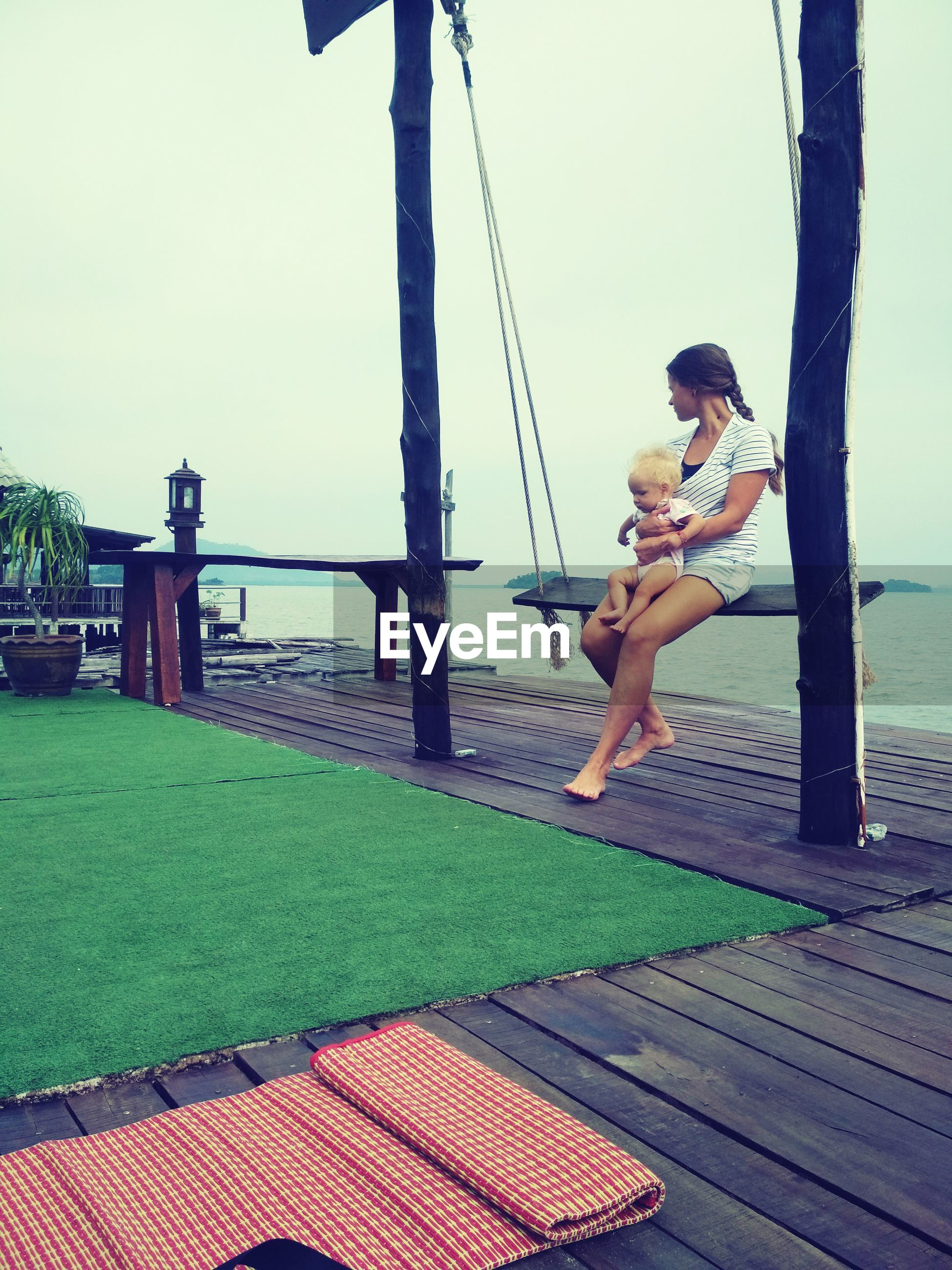 Woman with daughter sitting on swing at lake against sky
