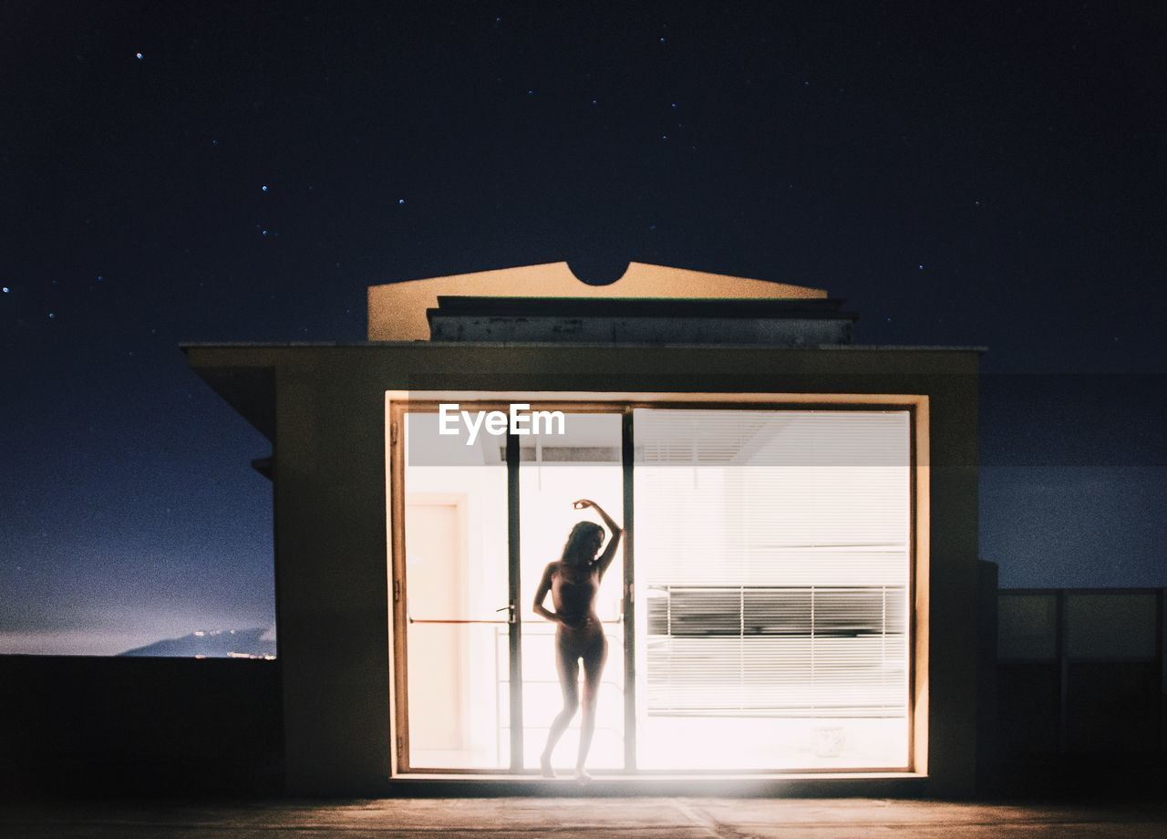 Woman Standing At Home Seen Through Window During Night