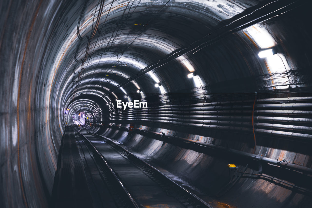architecture, tunnel, built structure, transportation, public transportation, indoors, arch, rail transportation, no people, illuminated, the way forward, track, direction, railroad track, motion, diminishing perspective, metal, mode of transportation, subway, travel, light at the end of the tunnel