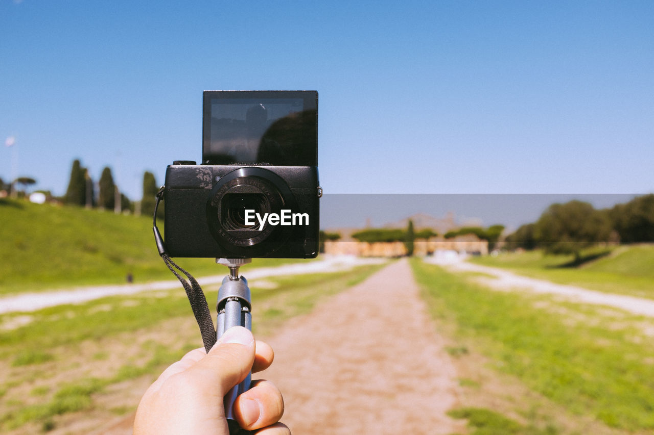 Cropped hand of man taking selfie from camera on monopod against sky