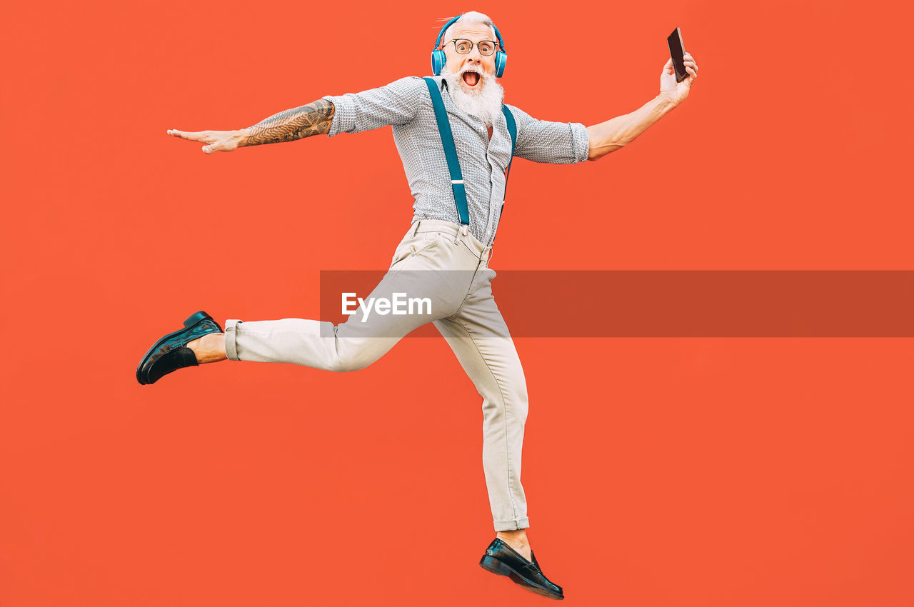colored background, studio shot, human arm, full length, red, one person, limb, arms raised, young adult, arms outstretched, indoors, mid-air, red background, jumping, lifestyles, happiness, cut out, copy space