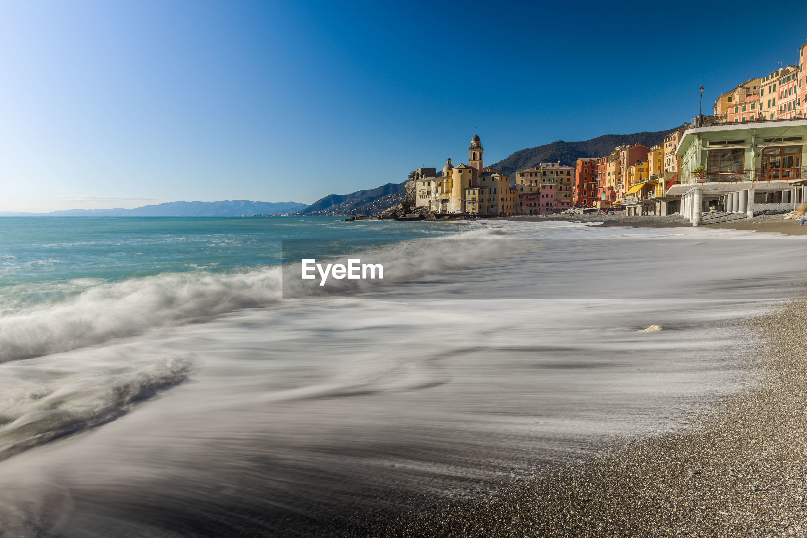 Scenic view of beach by city against clear blue sky