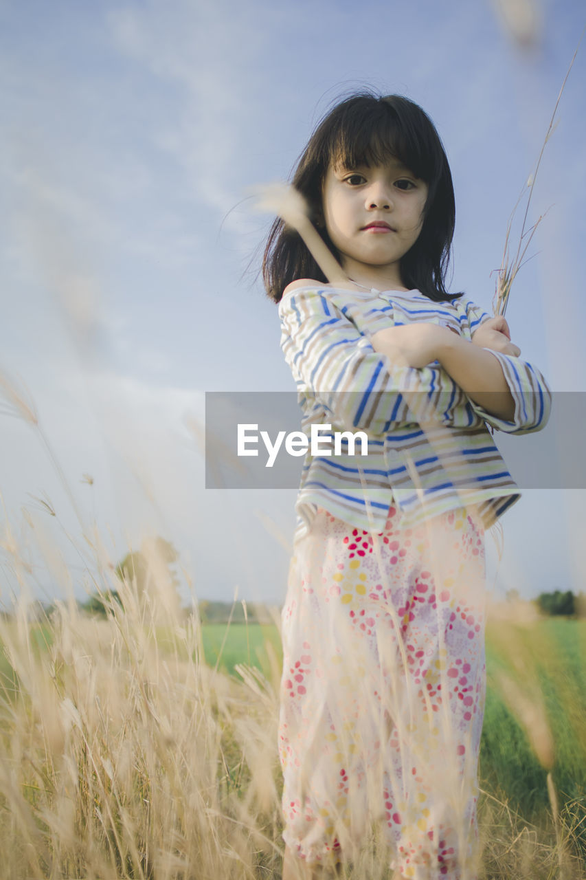 Low angle portrait of cute girl standing on grassy field against sky