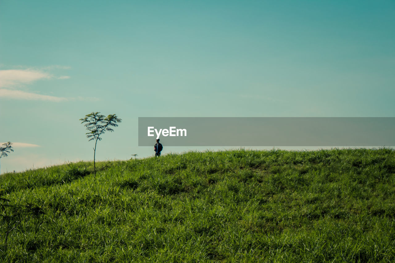 Low angle view of man standing on grassy field against sky