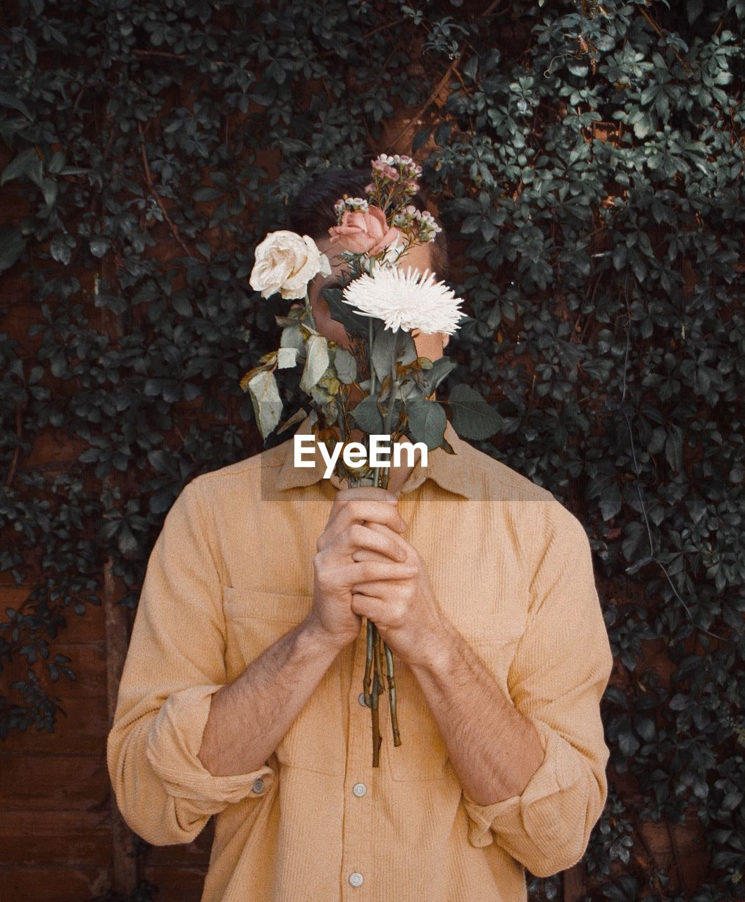 flower, flowering plant, plant, one person, holding, leaf, plant part, adult, nature, standing, obscured face, unrecognizable person, front view, beauty in nature, autumn, waist up, men, day, vulnerability, outdoors, contemplation, flower arrangement