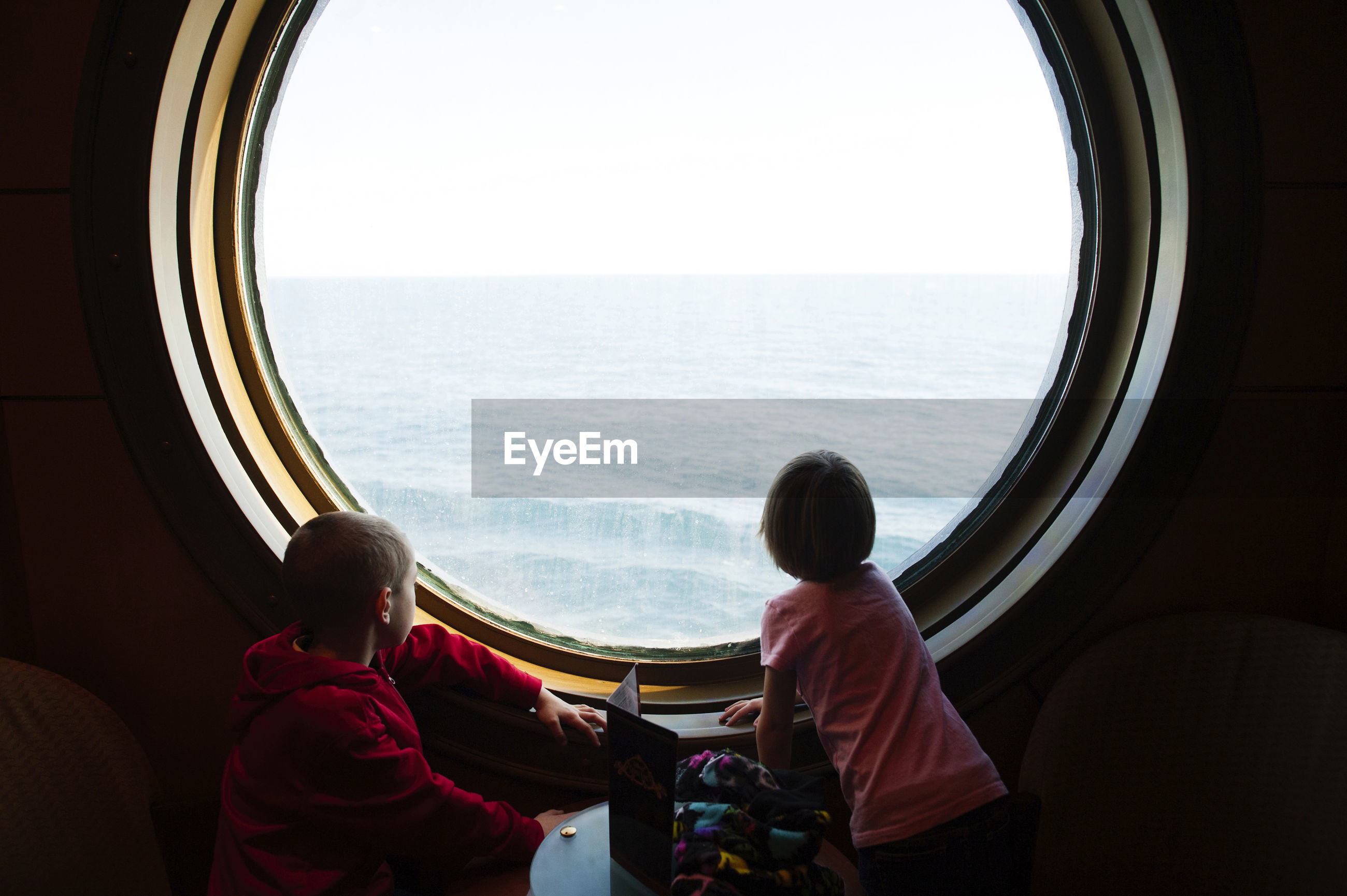 REAR VIEW OF TWO PEOPLE LOOKING AT SEA