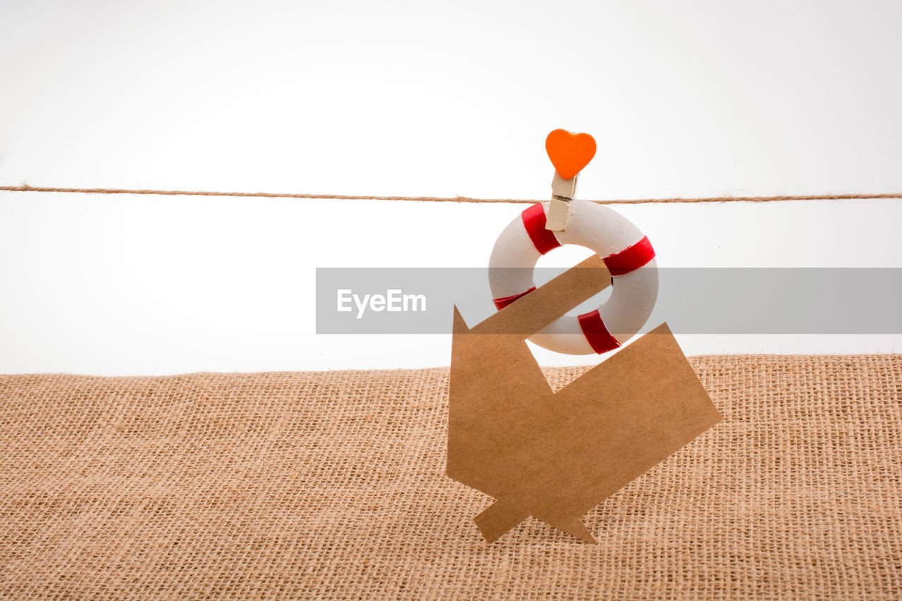 paper, indoors, still life, studio shot, copy space, red, no people, white background, string, container, box, wall - building feature, cardboard, close-up, shape, hanging, wood - material, decoration, nature