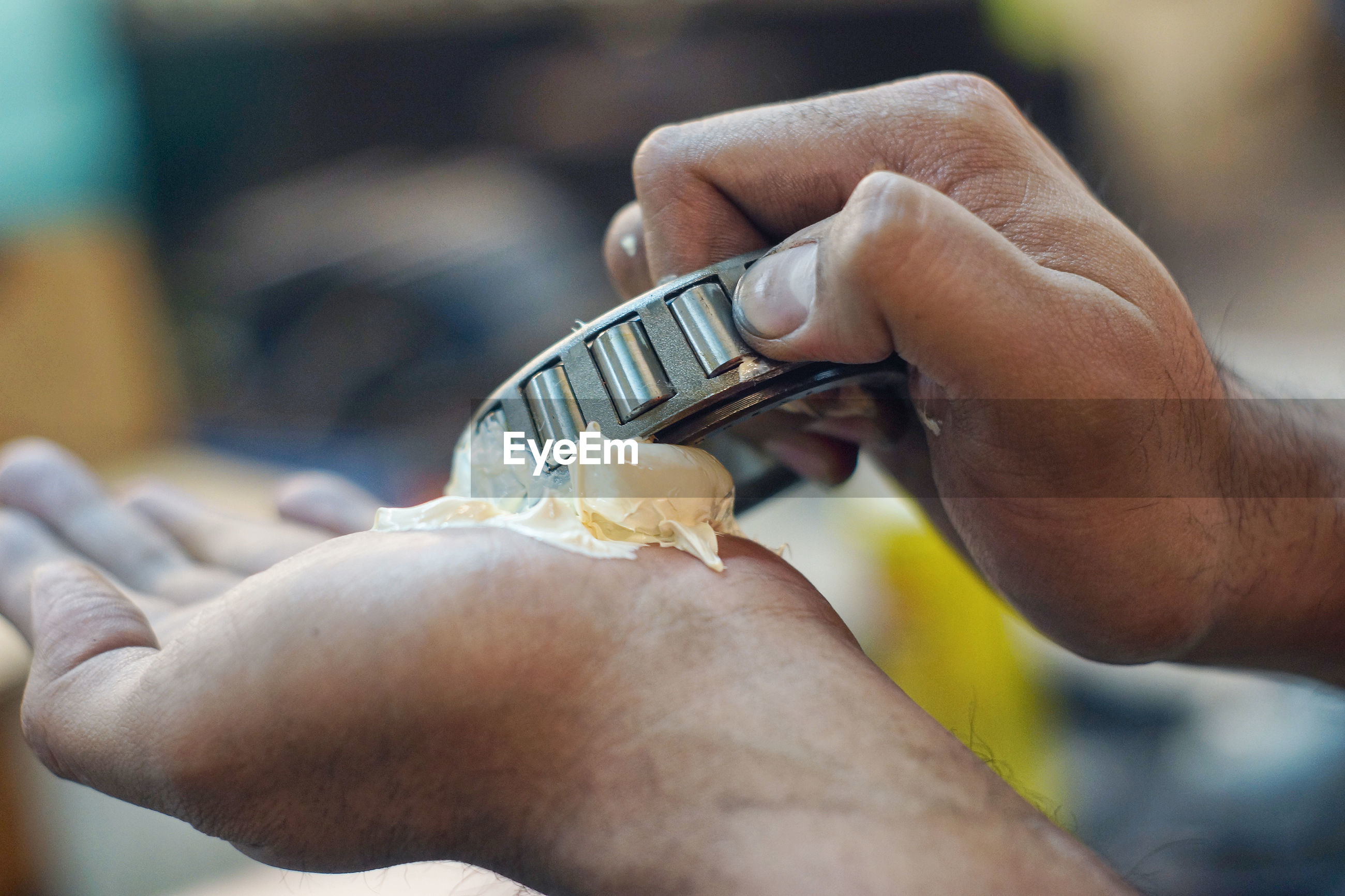 Cropped hands of mechanic holding tool and grease