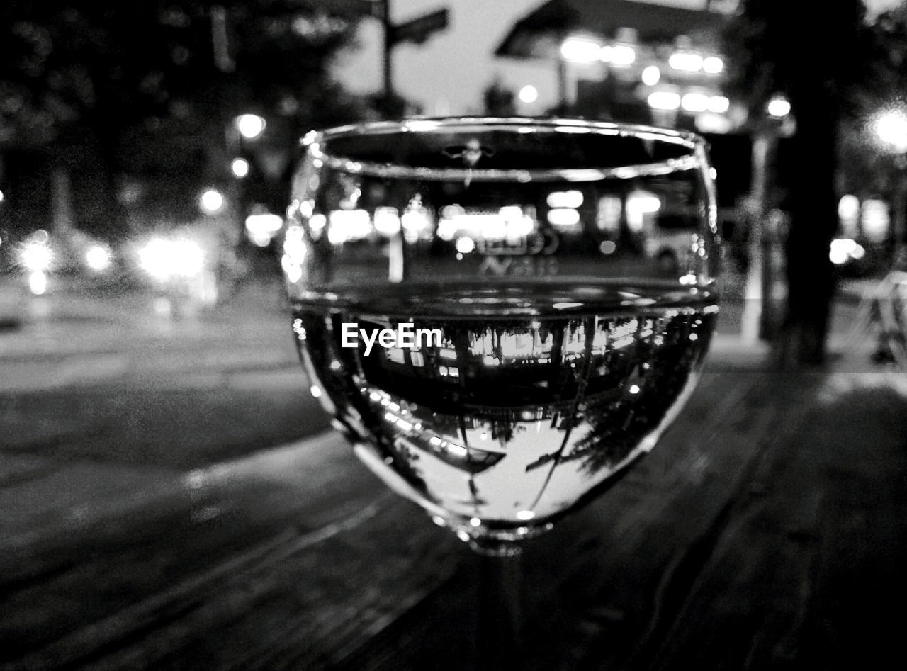 focus on foreground, close-up, illuminated, night, table, no people, alcohol, refreshment, outdoors, drink, wineglass, nature, freshness