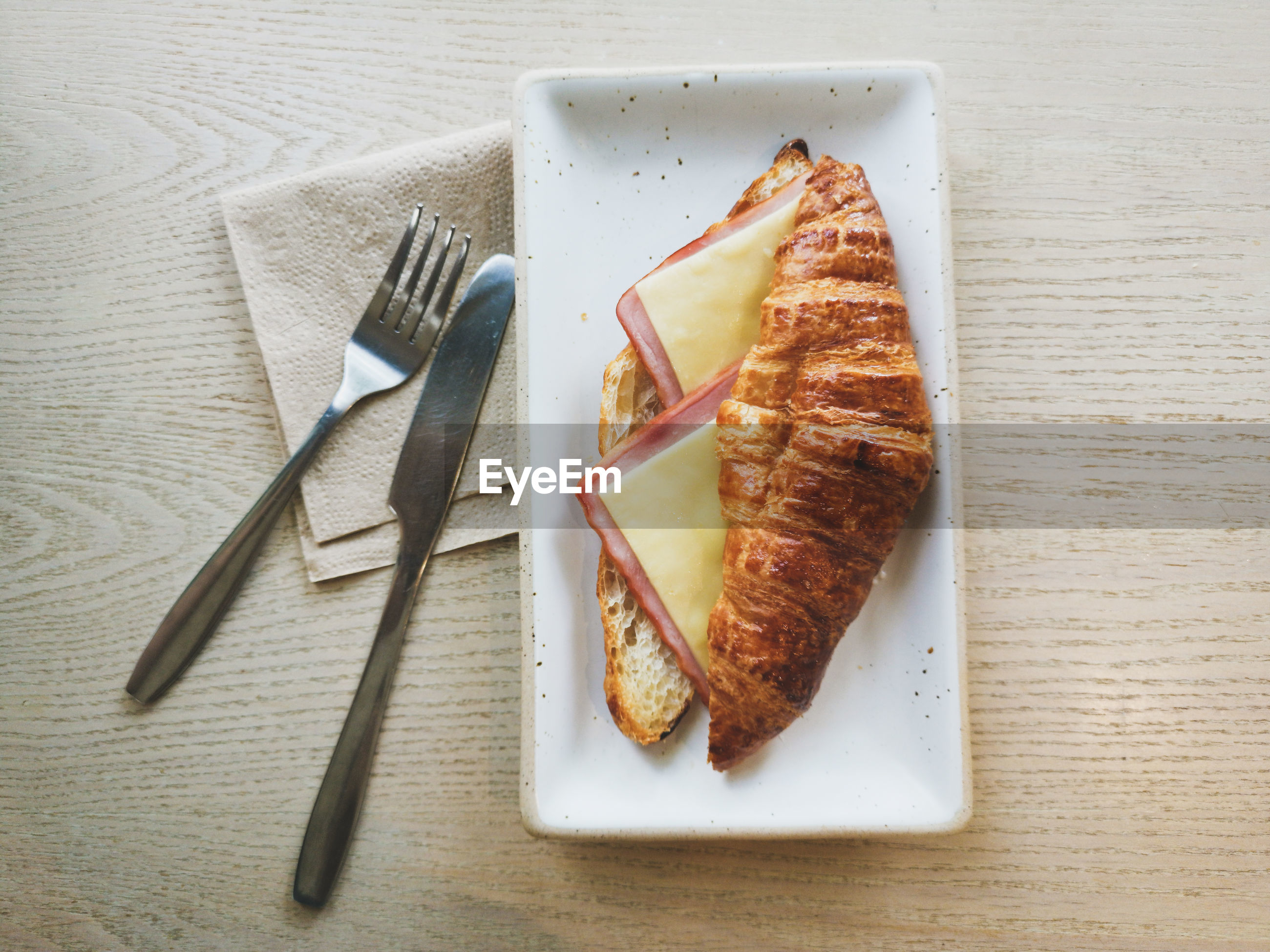 Croissant sandwich ham cheese on wooden table and fork knife