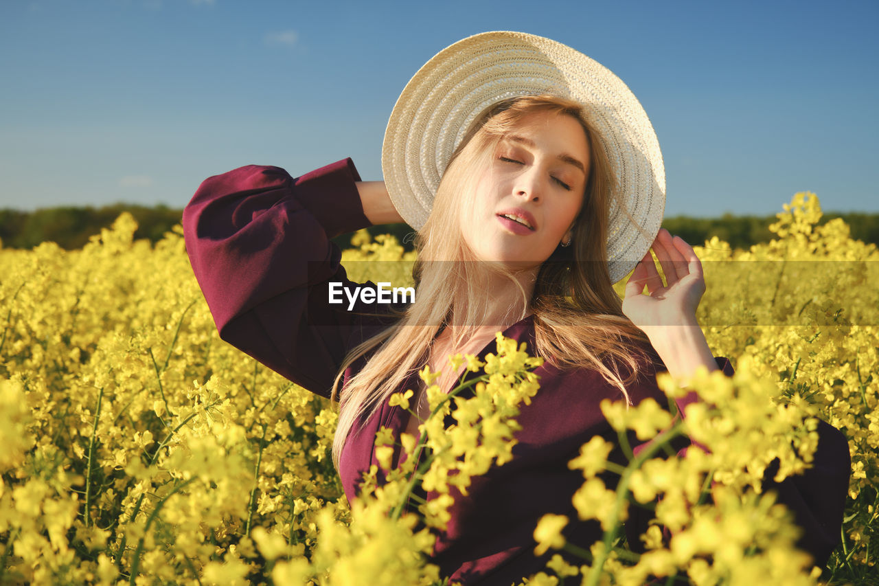 Happy young attractive woman in hat and purple dress on rapeseed field