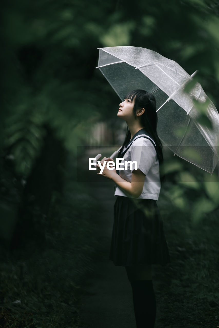 one person, umbrella, holding, standing, real people, women, lifestyles, rain, protection, wet, leisure activity, focus on foreground, day, monsoon, nature, casual clothing, side view, rainy season, outdoors, innocence