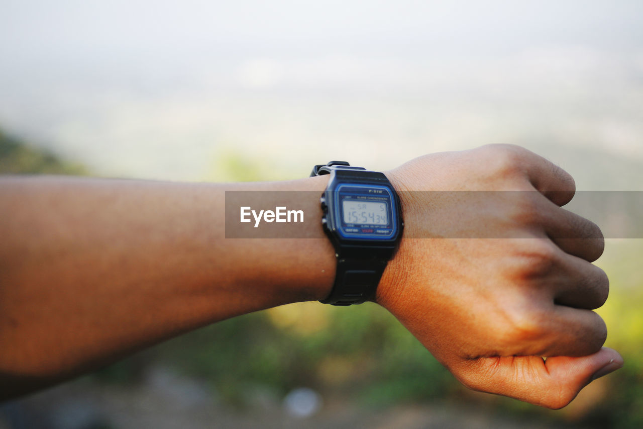 Close-up of hand using wristwatch