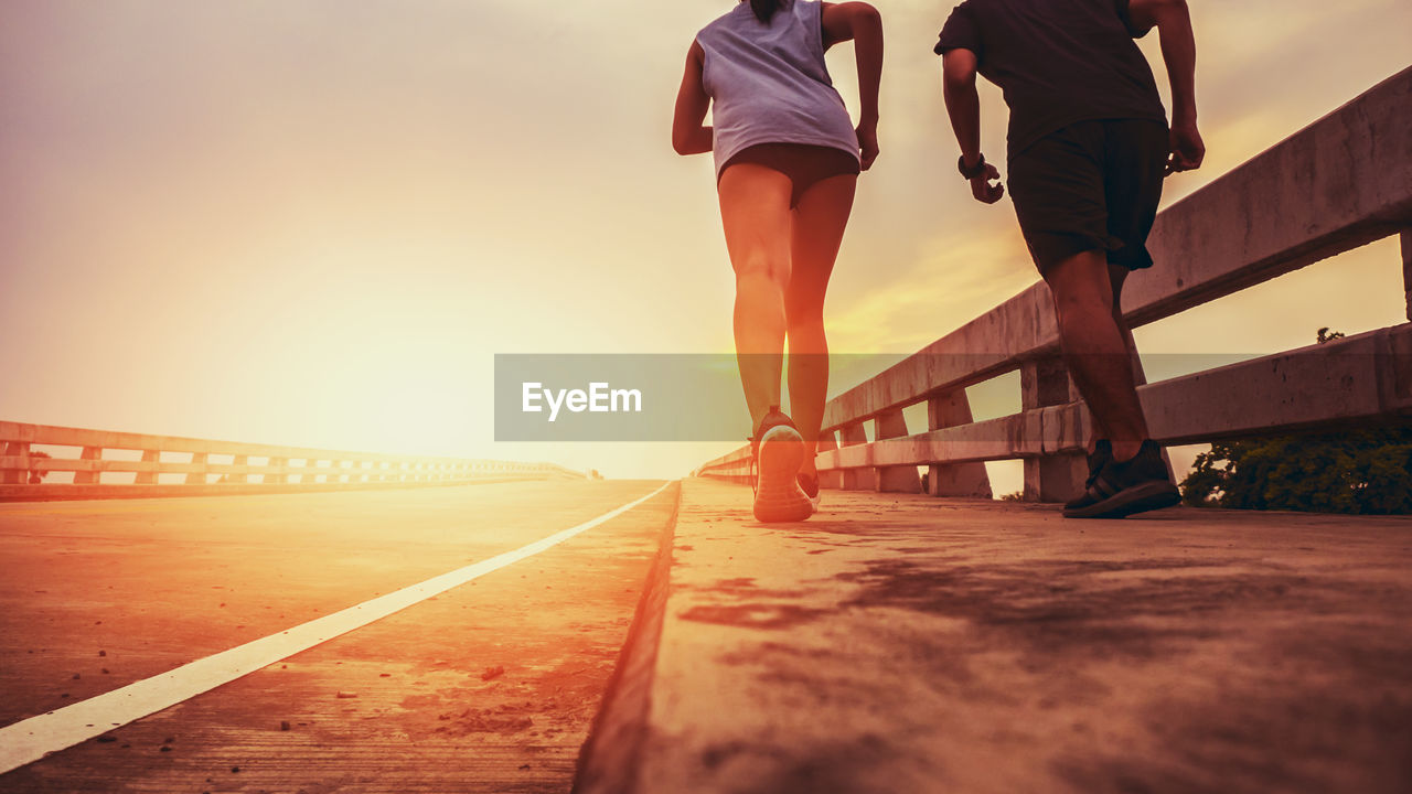 sunset, lifestyles, sky, real people, men, women, leisure activity, nature, low section, adult, walking, people, two people, human leg, transportation, railing, rear view, sunlight, human body part, selective focus, surface level, outdoors, bridge - man made structure, shorts