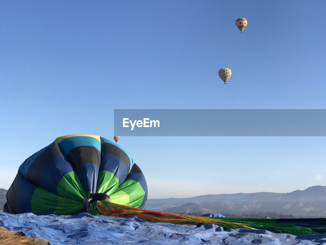 Men with hot air balloon on mountain against clear sky