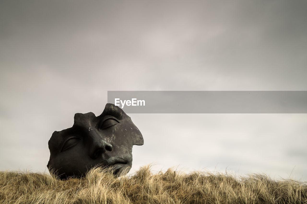 Close-Up Of Broken Sculpture On Field Against Sky