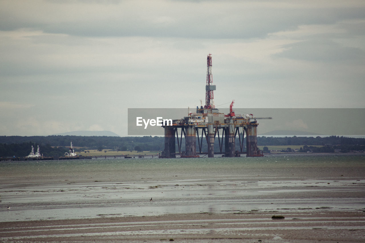 Oil Drill Amidst Sea Against Sky