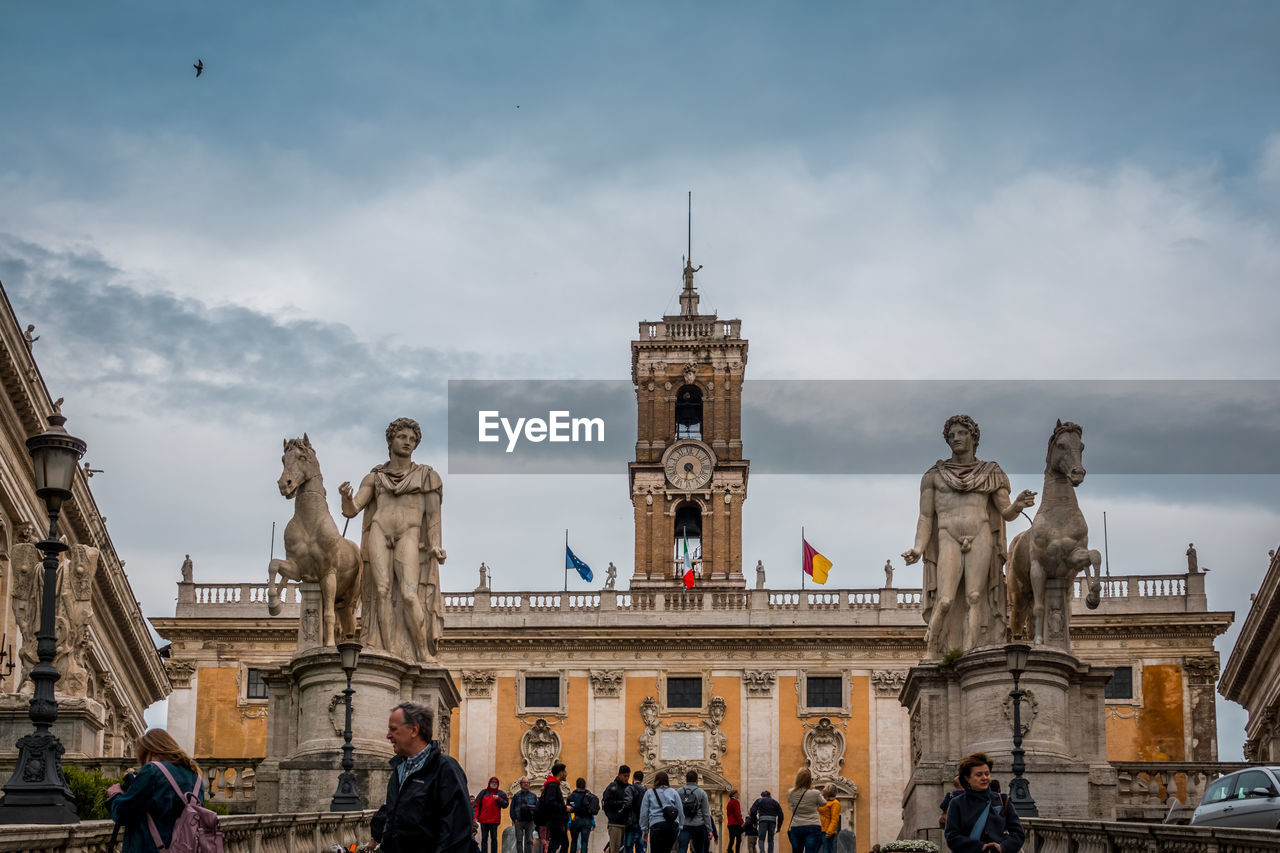 architecture, sculpture, statue, sky, built structure, art and craft, travel destinations, building exterior, representation, human representation, tourism, the past, history, travel, large group of people, group of people, real people, creativity, cloud - sky, male likeness, outdoors, architectural column