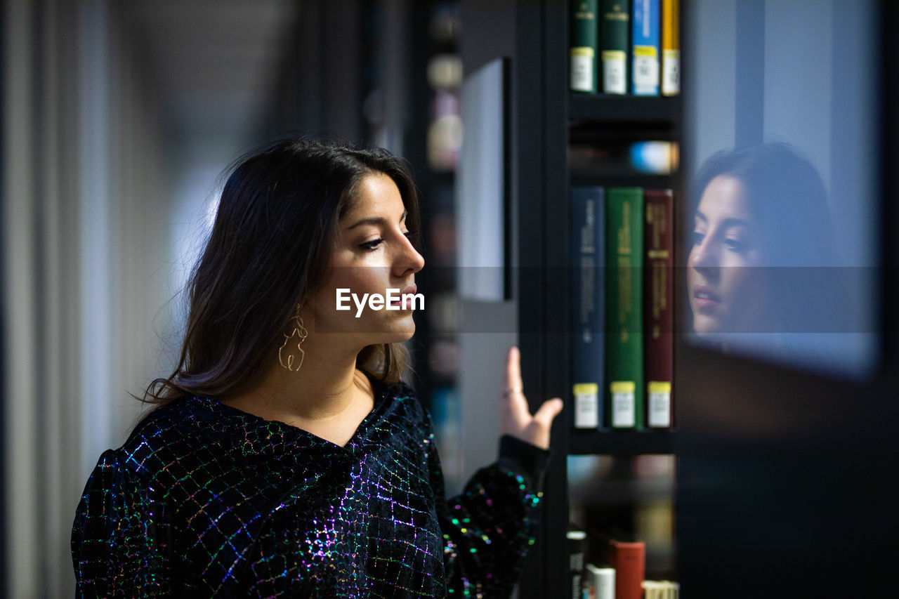 Young woman looking away while standing in library