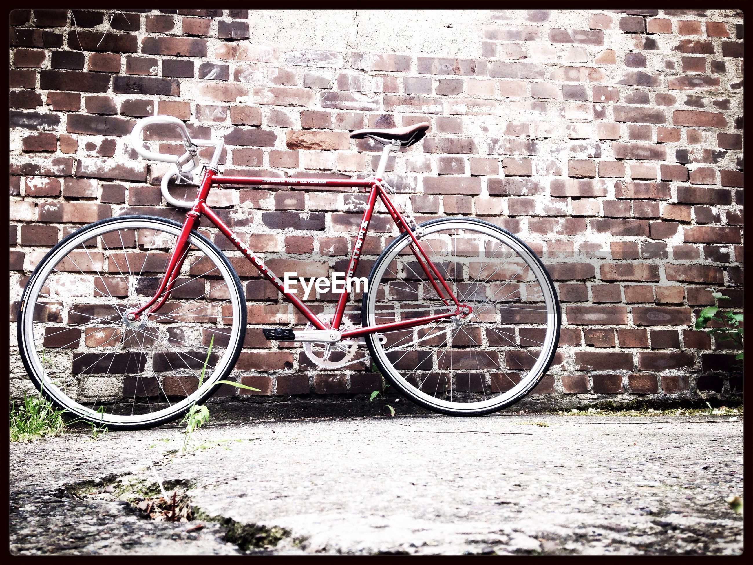 bicycle, wall - building feature, built structure, architecture, transportation, brick wall, building exterior, graffiti, wall, stationary, mode of transport, day, auto post production filter, transfer print, land vehicle, outdoors, parked, abandoned, stone wall, no people