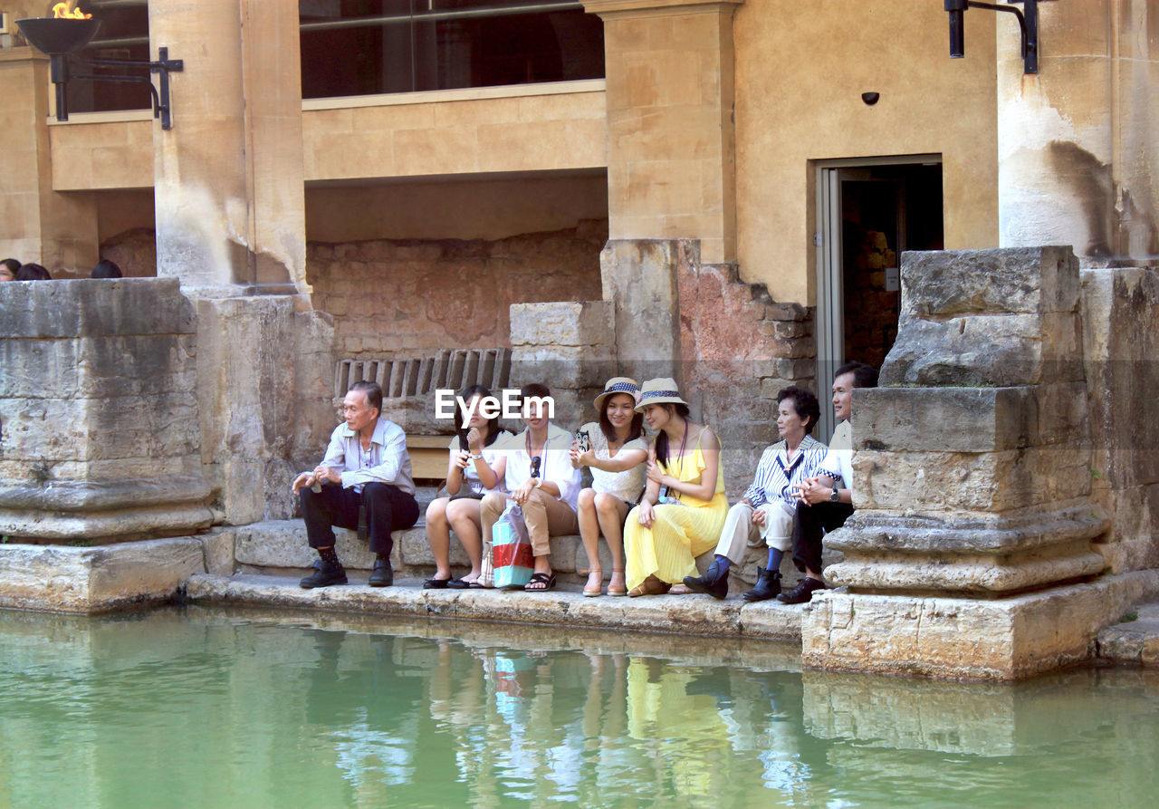 group of people, architecture, water, building exterior, young adult, men, women, full length, day, adult, built structure, people, sitting, group, reflection, medium group of people, togetherness, travel destinations, outdoors, mature men