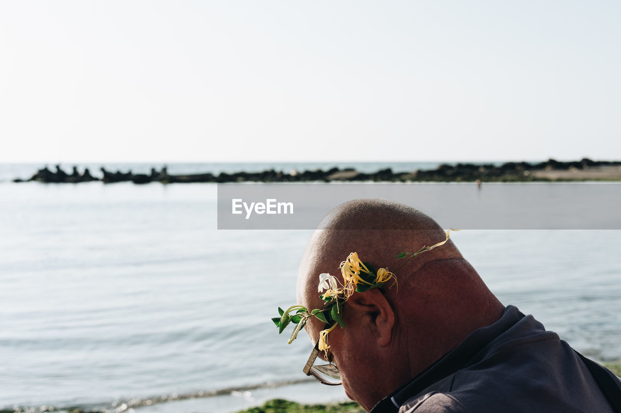 Close-Up Of Bald Man Wearing Flowers Against Sea