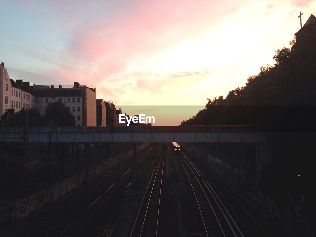 Railroad tracks by buildings against sunset sky