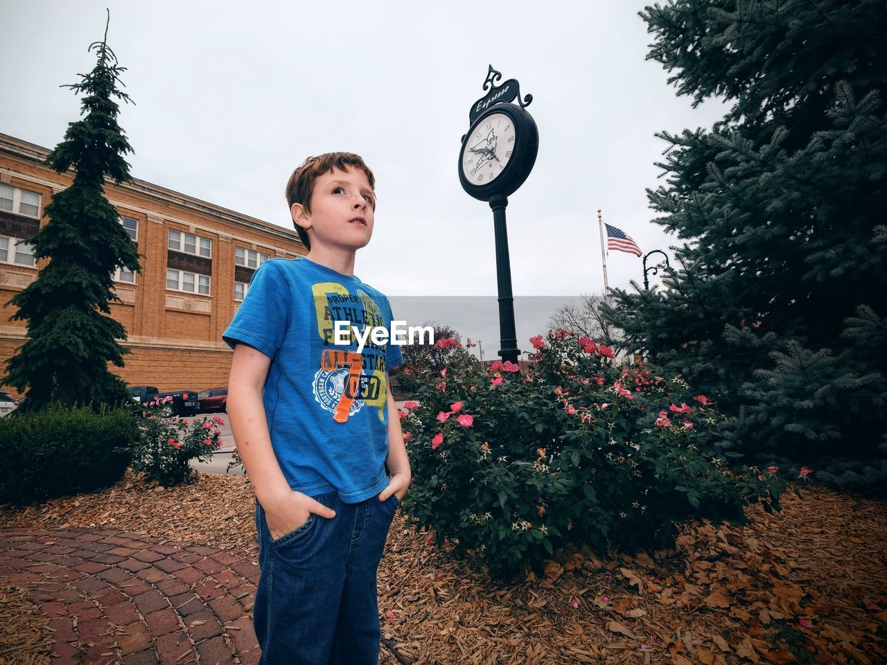 Boy with hands in pockets standing by clock against building