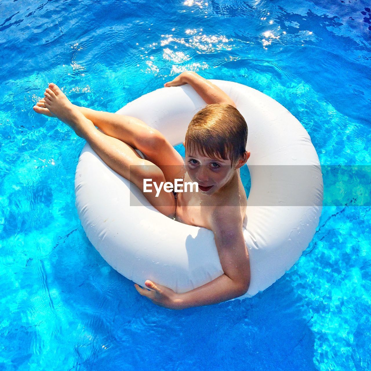 High Angle Portrait Of Boy With Inflatable Ring Floating On Swimming Pool