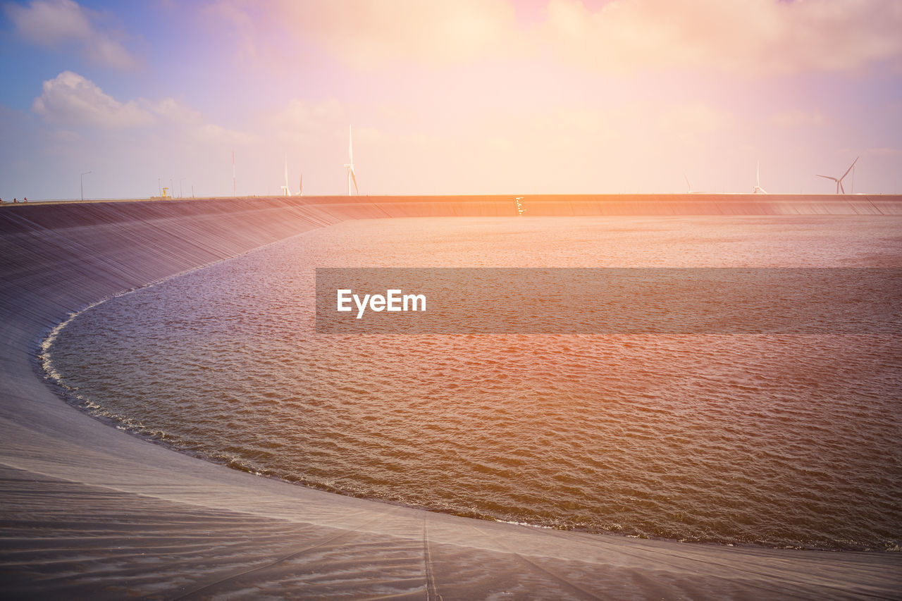 sky, sand, scenics - nature, beauty in nature, land, nature, water, sunset, tranquil scene, tranquility, no people, cloud - sky, sea, environment, renewable energy, wind turbine, outdoors, environmental conservation, beach, arid climate