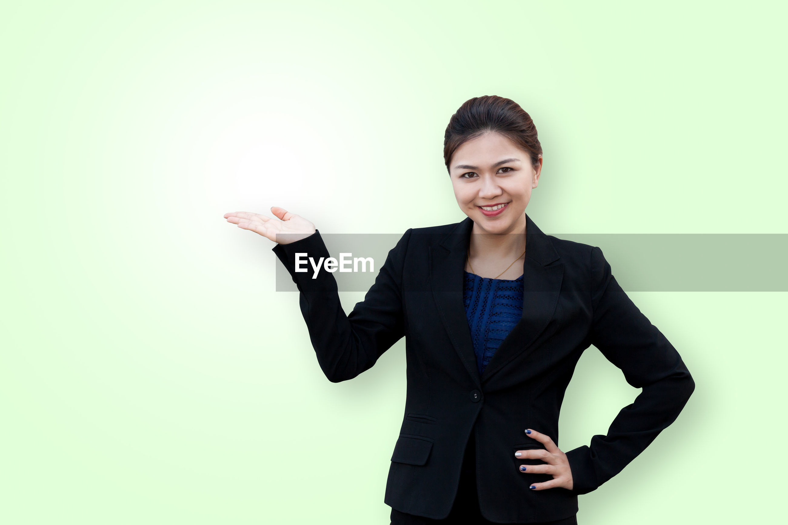 Portrait of businesswoman standing against wall