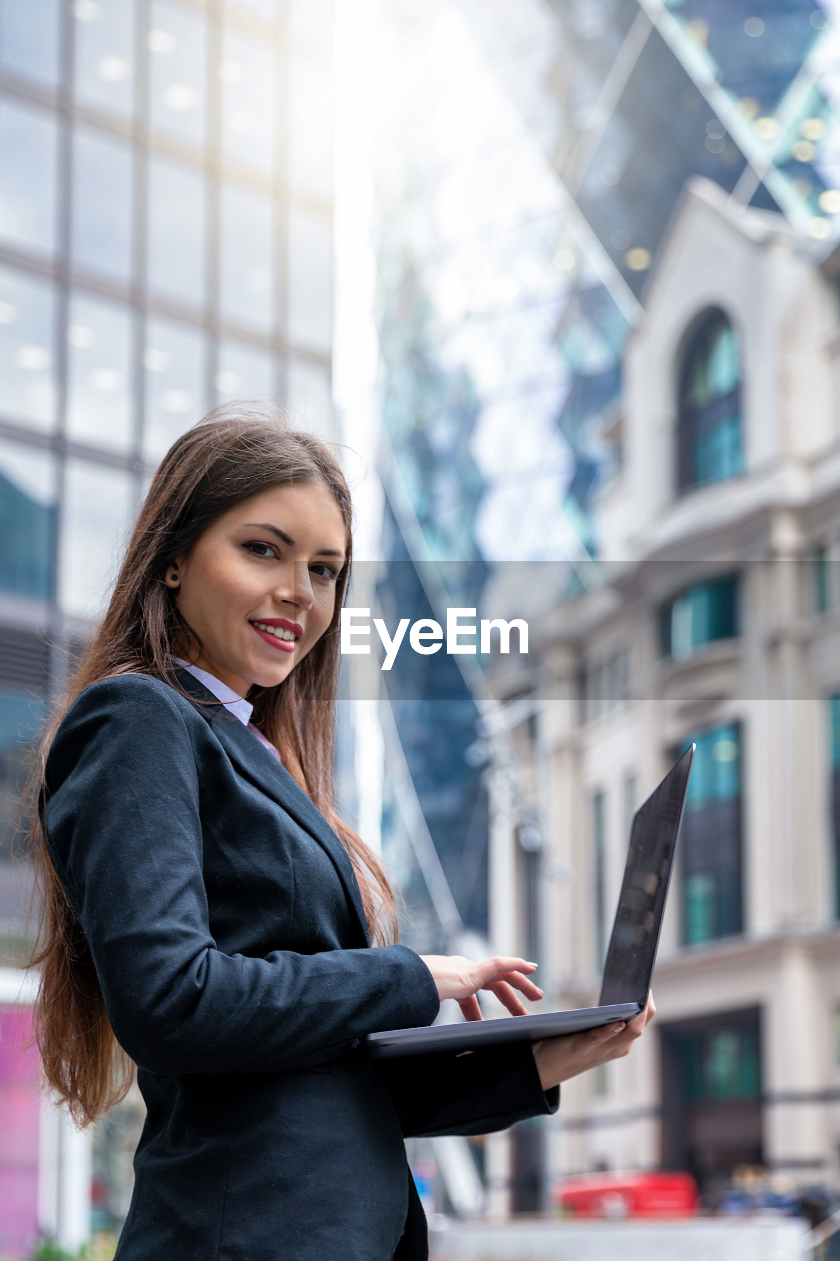 Portrait of confident young businesswoman using laptop in city